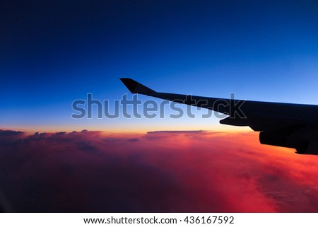 Air plane's wing with morning glow above the clouds
