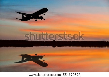 Air plane silhouette over the sunset cloud with reflection on lake