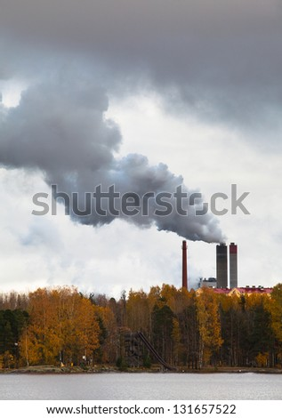 Air pollution by smoke coming out of three factory chimneys. - stock photo