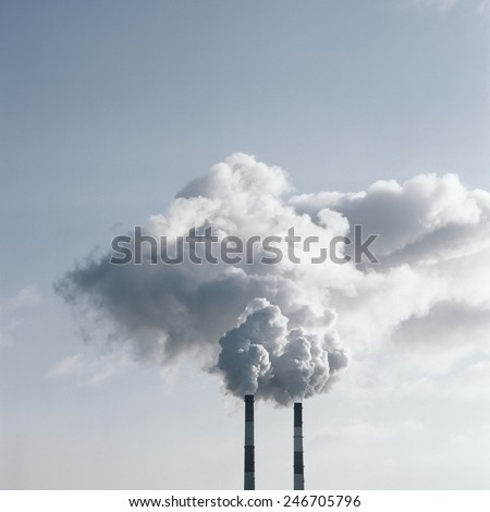 Air pollution by smoke coming out of two factory chimneys. Scanned film source. - stock photo