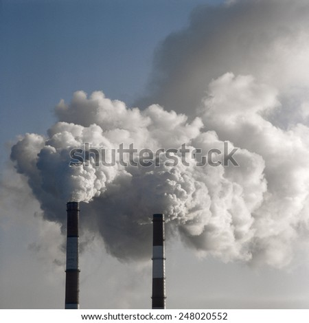 Air pollution by smoke coming out of two factory chimneys. Scanned film source.