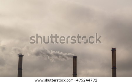 Air pollution from coal-powered plant smoke stacks, and industrial cityscape, on a gloomy, overcast day