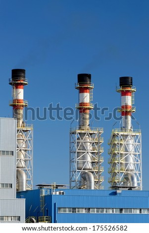 Air pollution of a factory with several chimneys - stock photo