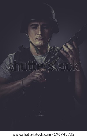 Air-soft, paintball sport player wearing protective helmet aiming pistol ,black armor and machine gun - stock photo