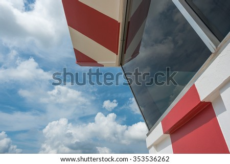 Air traffic control tower with red and white paint and scatterd cloud - stock photo