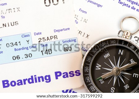 Air travel boarding pass and compass, close-up - stock photo