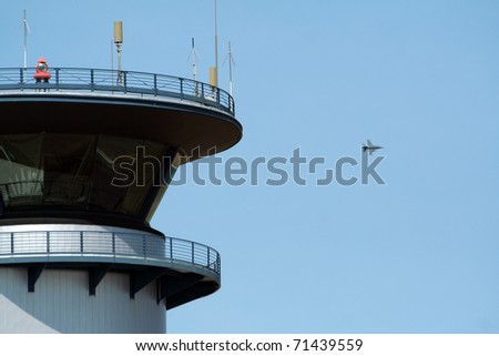 Airbase tower and F-16 jetfighter flyby - stock photo