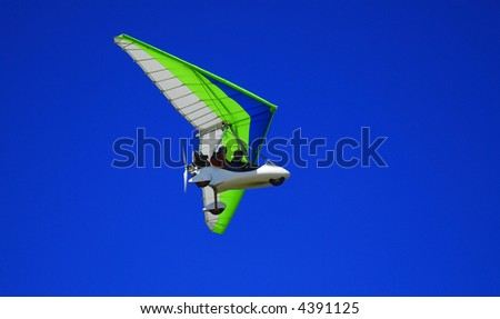 Airborne Motorized Ultralight Glider in a cloudless blue sky. - stock photo