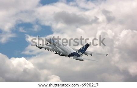 Airbus A380 flying into the clouds - stock photo