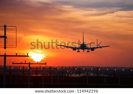aircraft approach during sundown - stock photo