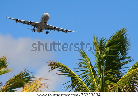 Aircraft approaching on final over tropical island - stock photo