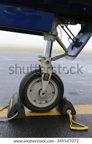 Aircraft front landing gear standing on the yellow line - stock photo