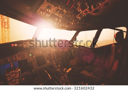 Aircraft interior, cockpit view inside the airliner. Point of view from a pilot place in a plane. Sunny sky horizon view from an airplane front glass. - stock photo