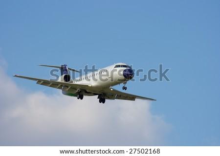 Aircraft landing against blue sky - stock photo