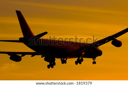 Aircraft landing in sunset - stock photo