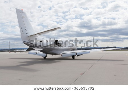 Aircraft learjet Plane in front of the Airport with cloudy sky and sun - stock photo