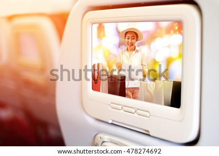 Aircraft monitor in front of passenger seat showing a happy shopaholic women opening a shopping bag