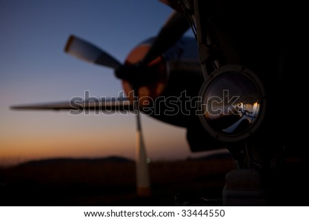 Aircraft nose engine and wing against setting sun skyline