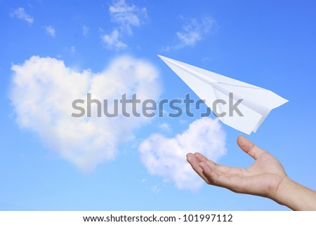 Aircraft paper hand blue sky with clouds, heart of love. - stock photo