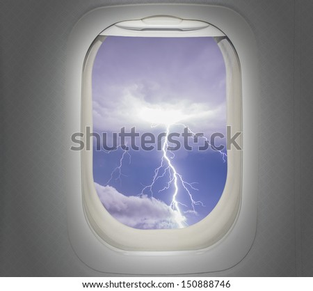 Aircraft window with view of lightning strike - stock photo