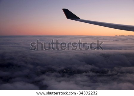 Aircraft wing in flight  Night light still below the clouds - stock photo