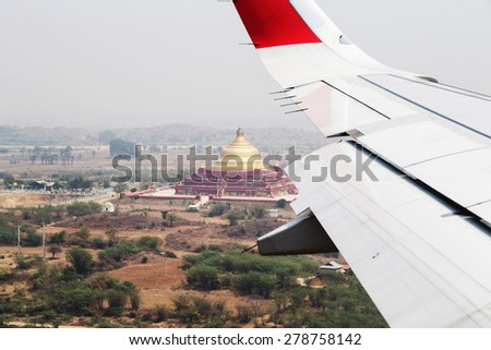 Aircraft wing on the clouds, landing in Mandalay, flying background Myanmar. - stock photo