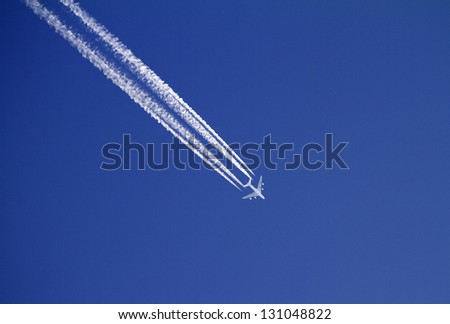 Aircraft with condensation trails on blue sky. - stock photo