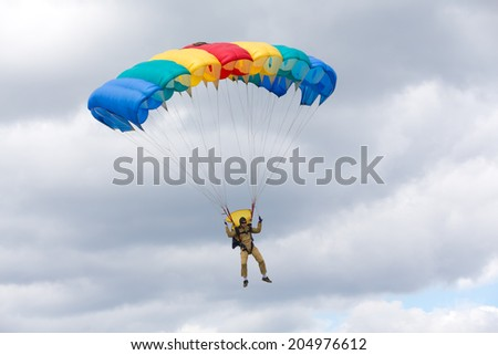 "Airfield Frolovo,Russia - June 29,2014.Festival ""Wings of Parma 2014"".skydiver fly on bright parachute"