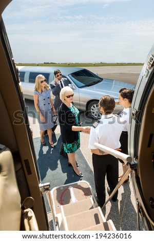 Airhostess and pilot greeting corporate people before boarding private jet - stock photo