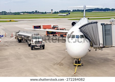 Airline Being Serviced Between Flights While Another One Lands / Doing Maintenance On Airplane  - stock photo