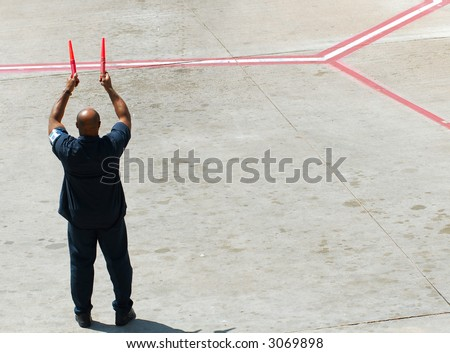 Airline ground crew directing an aircraft to the airport gate - stock photo