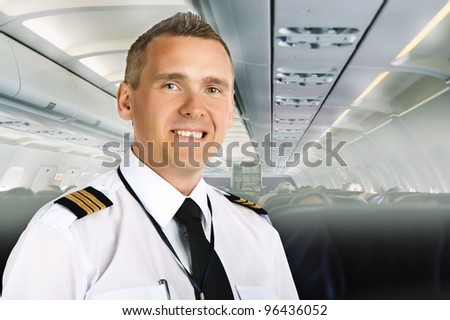 Airline pilot wearing uniform with epaulettes on board of passenger aircraft. - stock photo