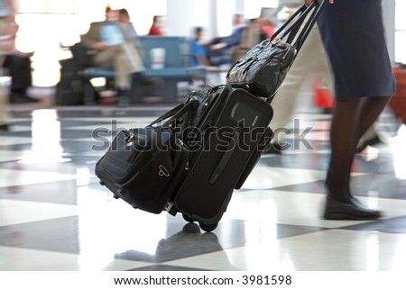 Airline travelers and passengers rush through the terminal to their flights with their baggage and luggage - stock photo