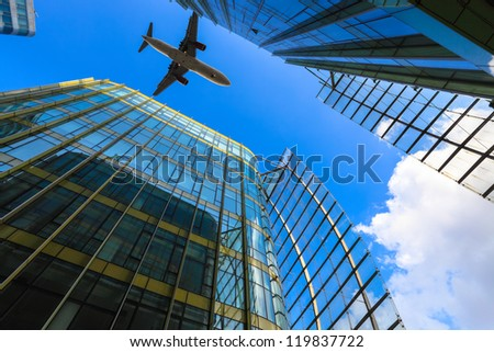 airliner and modern glass building against a blue sky - stock photo