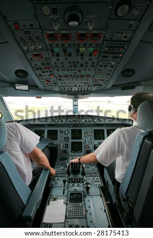 airliner cockpit at takeoff with two pilots - stock photo