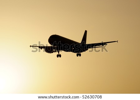 airliner flying into a sunset