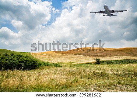 airliner flying over wheat fields