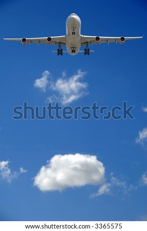 Airliner is going to land. A white cloud is in the background. - stock photo