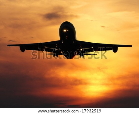 airliner landing at sunset, closeup - stock photo