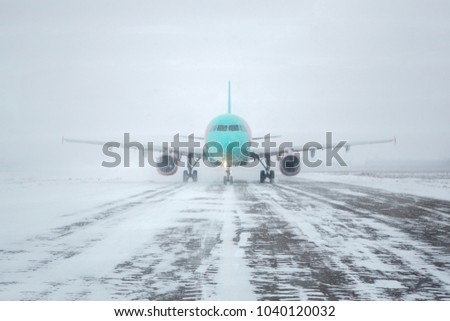 Airliner on runway in blizzard. Aircraft during taxiing at heavy snow. Passenger plane in snow at airport. Modern twin-engine passenger airplane taxiing for take off at airport during snow blizzard