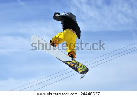 Airoski: a snowboarder in yellow pants hanging in the sky