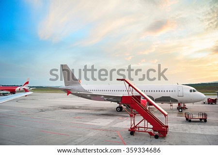 Airplaine at airport in the beautiful sunrise.  - stock photo