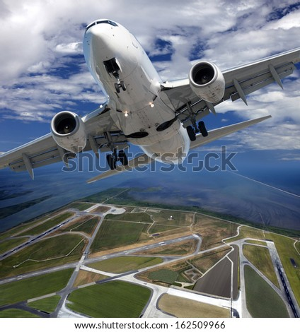 Airplane above airport - stock photo