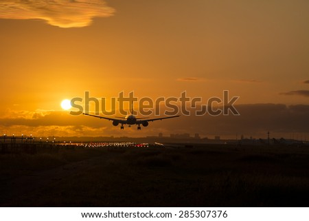 Airplane almost landed during a nice sunrise.