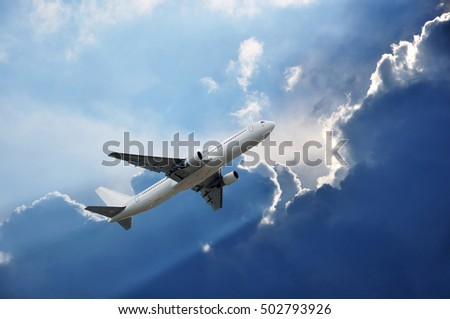 airplane and Sun lights an edge of blue cloud
