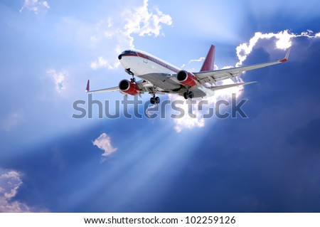 Airplane and  Sun rays going through dark clouds - stock photo