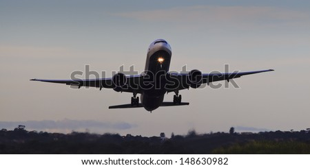 airplane at airport departuring airfield with trees underneaths going up sunset sky wide front view - stock photo