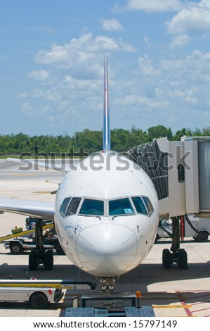 Airplane at airport gate, boarding and loading luggage - stock photo