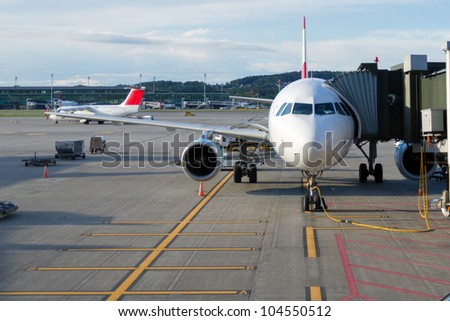 Airplane at an airport with passenger gangway - stock photo