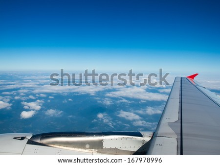Airplane at fly on the sky, view through aircraft window. - stock photo